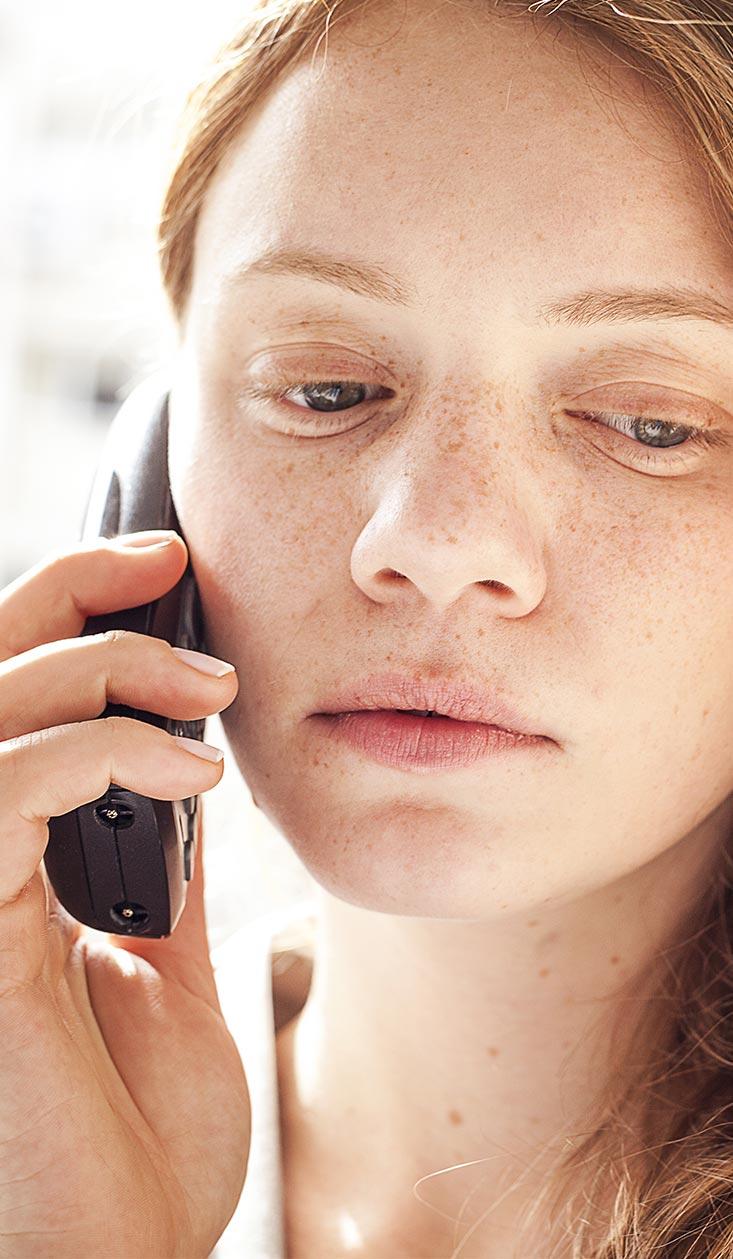Roodharig meisje met sproeten en telefoon
